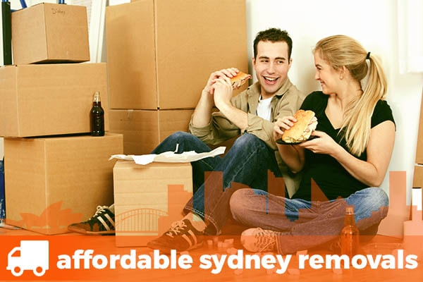 A Young couple surrounded by boxes having a quick lunch after using a Removalist in St George and Sutherland Shire area