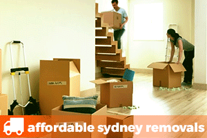 a man carrying a removalist box up a staircase with a woman packing another removalist box